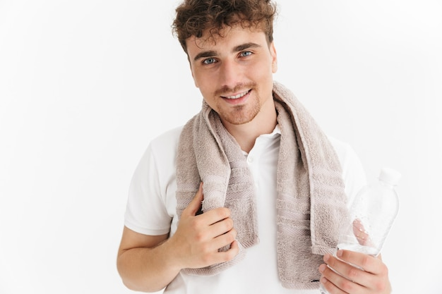 正面に笑みを浮かべて、白い壁の上に分離された水のボトルを保持しているタオルとポジティブな男の肖像画のクローズアップ