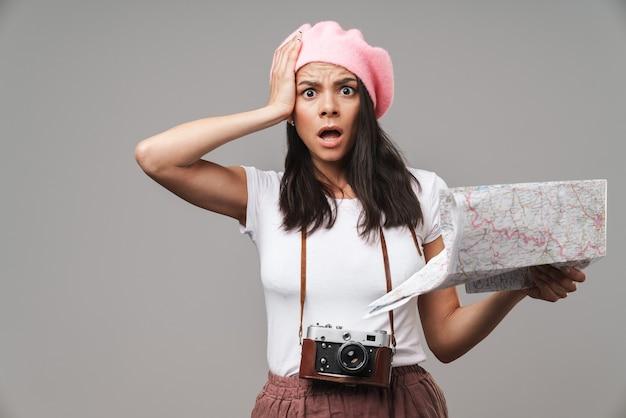 灰色の壁に分離された紙の地図を保持しながら彼女の頭をつかむレトロなビンテージカメラとショックを受けた若い観光客の女性の肖像画のクローズアップ