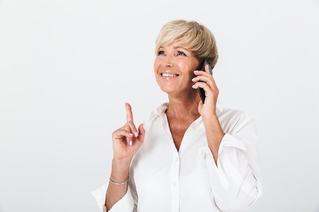 短いブロンドの髪と人差し指を上に向けて、スタジオの白い壁の上に隔離された携帯電話で話している笑顔の大人の女性の肖像画のクローズアップ