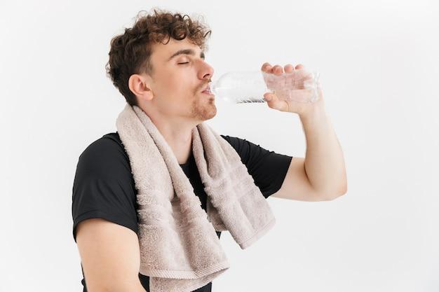 白い壁に隔離されたトレーニング後のペットボトルから水を飲むタオルで喉が渇いた若い男の肖像画のクローズアップ