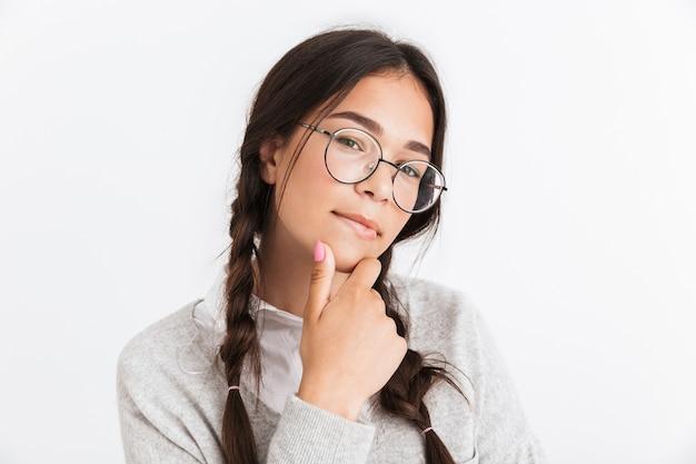 彼女のあごに触れて、白い壁に隔離されたカメラを見ている眼鏡をかけている思慮深い10代の少女の肖像画のクローズアップ