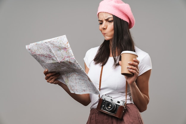 Portrait closeup of perplexed young tourist woman with retro vintage camera and takeaway coffee thinking and looking at paper map isolated over gray wall