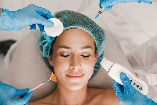 Portrait closeup of pleased caucasian woman getting cosmetic procedure and injection while lying in beauty salon