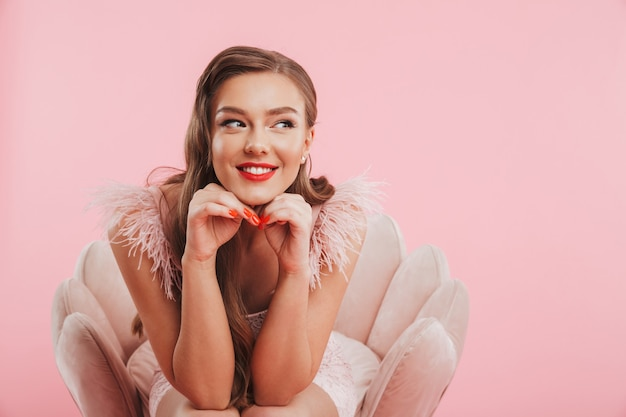 Portrait closeup of pleased smiling woman in dress propping her head while sitting in armchair, isolated over pink wall