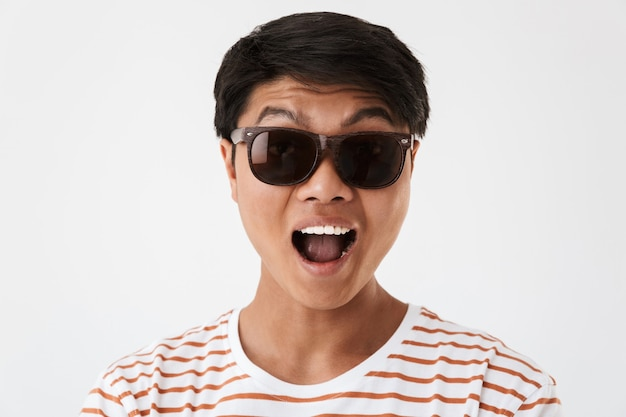 Portrait closeup of positive chinese man wearing striped t-shirt and black eyeglasses smiling or screaming and looking at you, isolated. concept of emotions