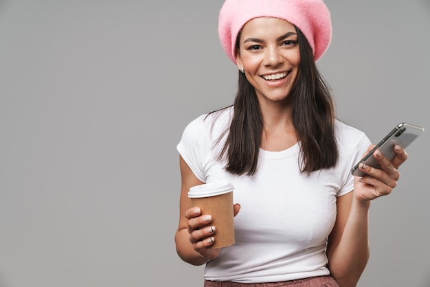Portrait closeup of positive pretty woman in beret smiling and holding smartphone while drinking takeaway coffee isolated over gray wall