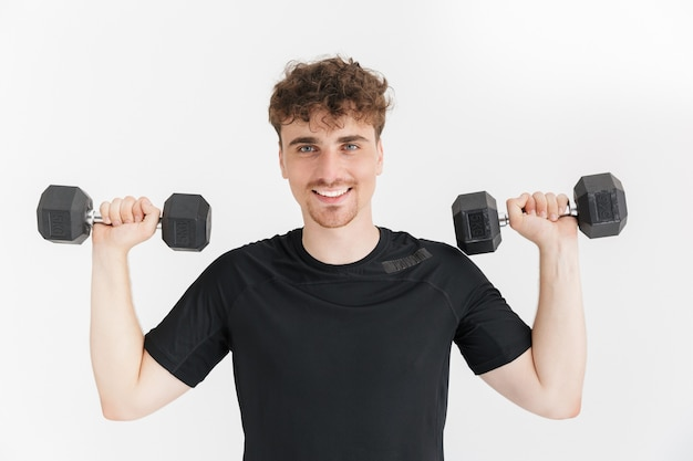 Portrait closeup of satisfied sporty man in t-shirt looking at front and lifting dumbbells during workout isolated over white wall