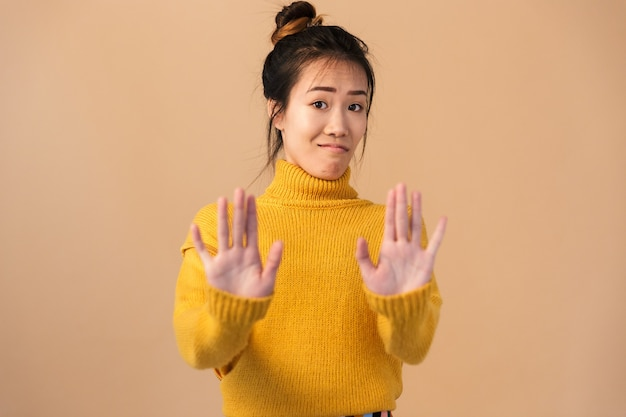 Portrait closeup of serious chinese woman wearing sweater doing stop gesture with hands isolated over beige wall in studio