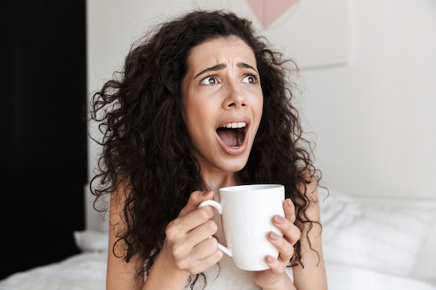 Portrait closeup of shocked or scared woman with long curly hair sitting on bed with white clean linen at home in morning, and holding cup of tea