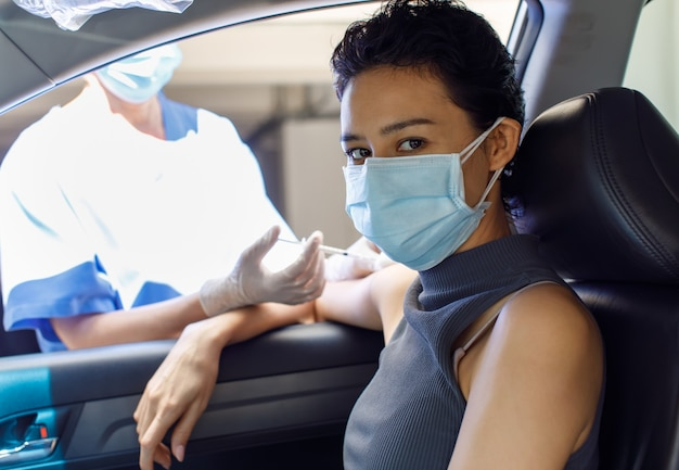 Portrait closeup shot of female patient sit in car look at camera receiving coronavirus vaccine injection on shoulder from syringe needle from doctor hand in hospital uniform and rubber gloves.