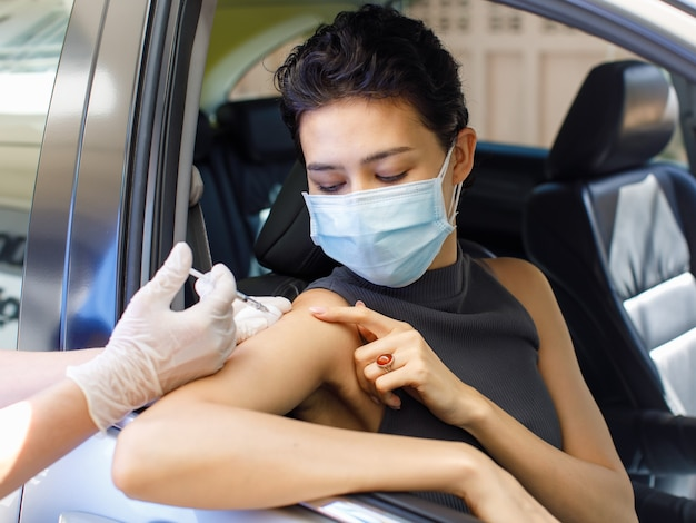 Portrait closeup shot of female patient sit in drive thru queue look at camera point and receive coronavirus vaccine injection shot on shoulder from syringe on doctor hand wears rubber gloves.