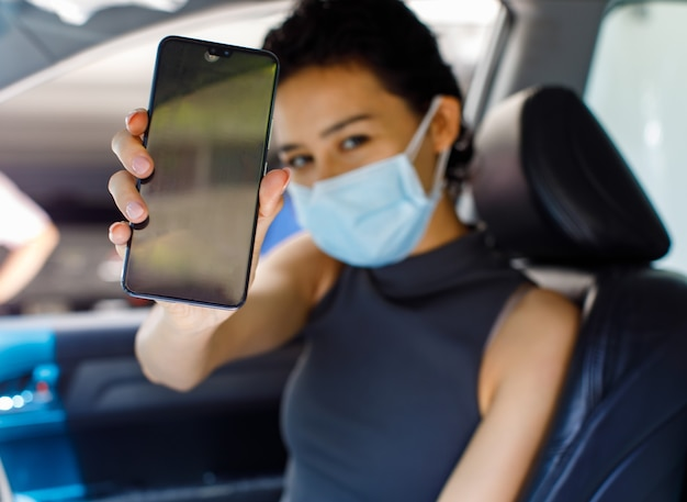 Portrait closeup shot of female wearing face mask sitting in car in drive through line for coronavirus vaccination holding blank black screen mobile phone for copy space in blurred foreground.