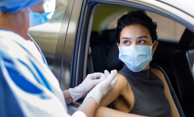 Portrait closeup shot of female wearing face mask sitting in car receiving coronavirus vaccine from doctor wears hospital uniform using syringe and needle in drive through vaccination queue.