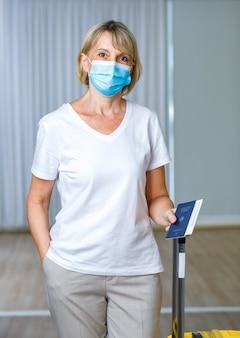 백인 고령 여성 환자의 초상화 클로즈업 사진은 코로나바이러스 백신을 받고 해외 여행을 떠날 준비가 된 후 파란색 코비드-19 예방 접종 기록 카드 여권과 수하물을 들고 얼굴 마스크를 착용합니다.