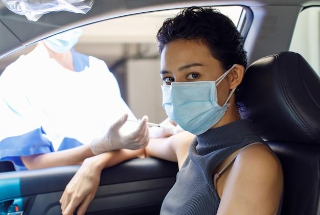 Портрет крупным планом пациентки, сидящей в машине, смотрит на камеру, получающую инъекцию вакцины против коронавируса на плечо из иглы шприца из руки врача в больничной форме и резиновых перчатках.