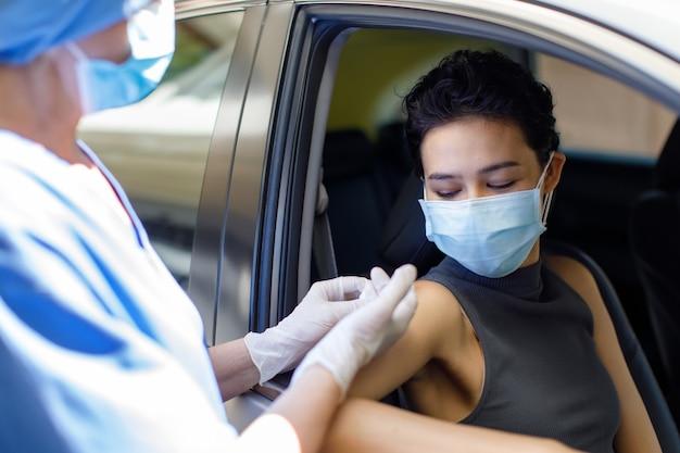 의사로부터 코로나바이러스 백신을 받는 차에 앉아 있는 얼굴 마스크를 쓴 여성의 초상화 클로즈업 샷은 백신 접종 대기열을 통해 드라이브에 주사기와 바늘을 사용하여 병원 유니폼을 착용합니다.