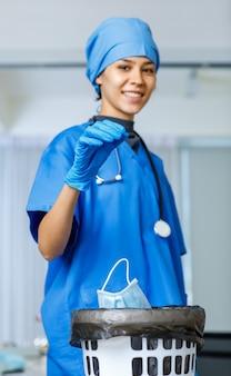 Снимок портрета крупным планом использованной хирургической маски для лица, сброшенной из счастливой красивой руки доктора свободы женщины в синей шляпе больничного костюма со стетоскопом, улыбающимся взглядом в камеру во время окончания пандемии covid.