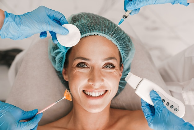 Portrait closeup of smiling caucasian woman getting cosmetic procedure and injection while lying in beauty salon