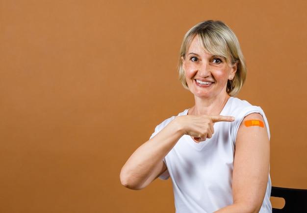 Portrait closeup studio shot of caucasian senior blonde female patient look at camera pointing finger at orange plaster bandage on her shoulder after receive coronavirus vaccinated.