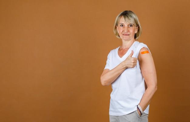 Portrait closeup studio shot of caucasian senior blonde female patient look at camera show thumb up at orange plaster bandage on her shoulder after receive coronavirus vaccinating.
