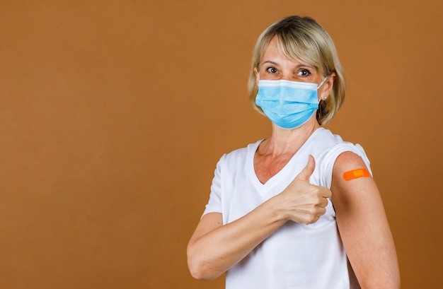Portrait closeup studio shot of caucasian senior blonde female patient wears face mask look at camera show thumb up at orange plaster bandage on her shoulder after receive coronavirus vaccinating.