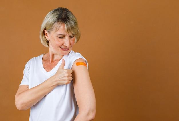 Portrait closeup studio shot of caucasian senior blonde female show thumb up at orange plaster bandage on her shoulder after receive coronavirus vaccinating.