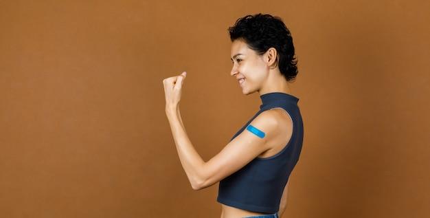 コロナウイルスcovid-19ワクチン接種を受けた後、彼女の肩に強い上腕二頭筋と青い石膏包帯を示して笑っている美しいセクシーな女性患者スタンドの肖像画のクローズアップスタジオショット。