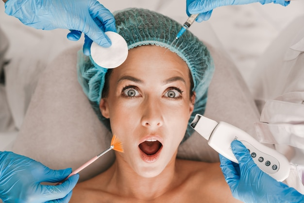 Portrait closeup of surprised caucasian woman getting cosmetic procedure and injection while lying in beauty salon