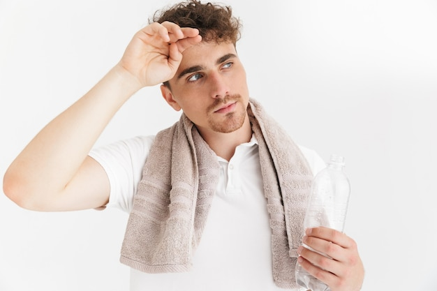 Portrait closeup of tired serious man with towel looking aside and holding water bottle isolated over white wall