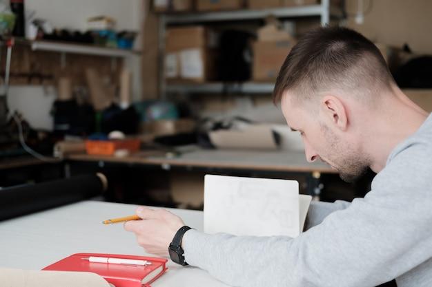 Portrait of a clothing designer or engineer at a generic workshop.