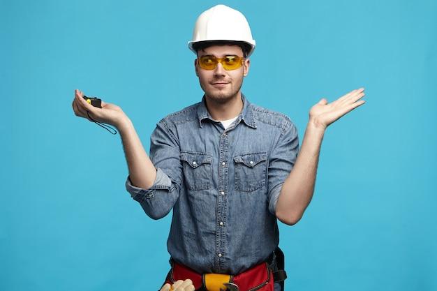 Ritratto di giovane costruttore confuso senza tracce in occhiali protettivi