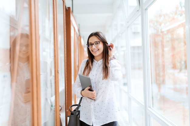 Portrait of collage girl standing next to noticeboard with tablet in arm and bag on the shoulder