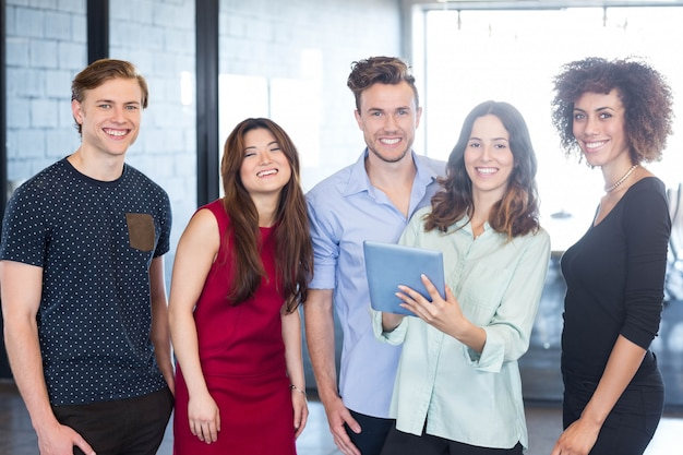 Portrait of colleagues holding digital tablet and smiling in office