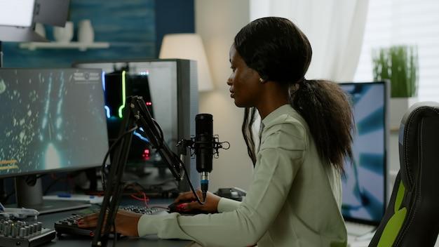 Ritratto di un giocatore africano concentrato che guarda la telecamera sorridendo, giocando a un videogioco sparatutto spaziale online per un torneo di gioco. cyber performance su pc potenti con videogame in streaming da tastiera rgb