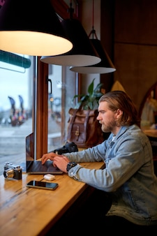 Portrait of concentrated bearded male photographer journalist sitting at cafe working