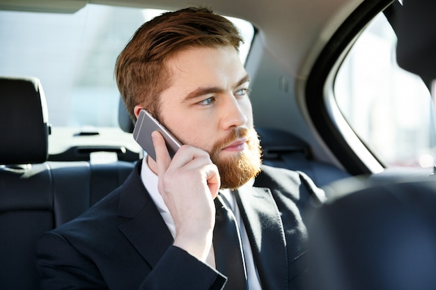 Portrait of a concentrated business man talking on mobile phone