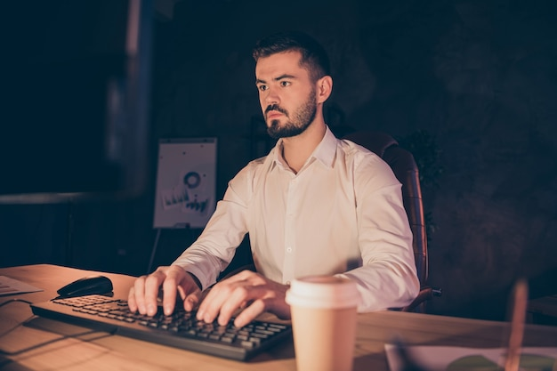 Portrait of concentrated businessman stay at night in dark office working on computer