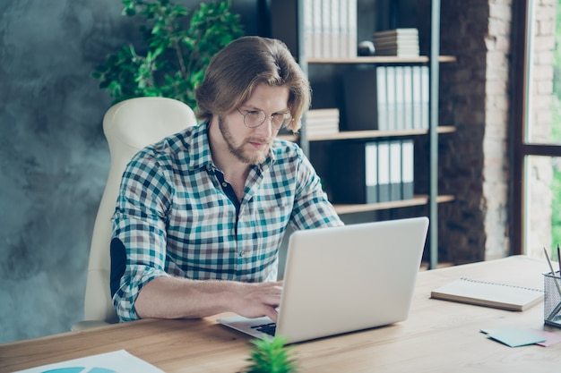 Portrait of concentrated employee working in the office on laptop