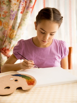 Portrait of concentrated girl drawing on canvas by oil paints