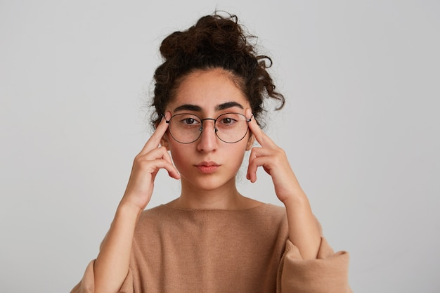 Portrait of concentrated pensive georgian young woman with curly hair wears beige pullover and glasses touching her temples and thinking isolated over white wall
