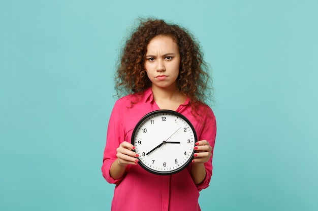 Portrait of concerned african girl in pink casual clothes holding round clock isolated on blue turquoise wall background in studio. people sincere emotions, lifestyle concept. mock up copy space.