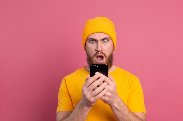 Portrait of concerned shocked mature bearded male gasping unhappy holding smartphone reading strange and disturbing message on pink