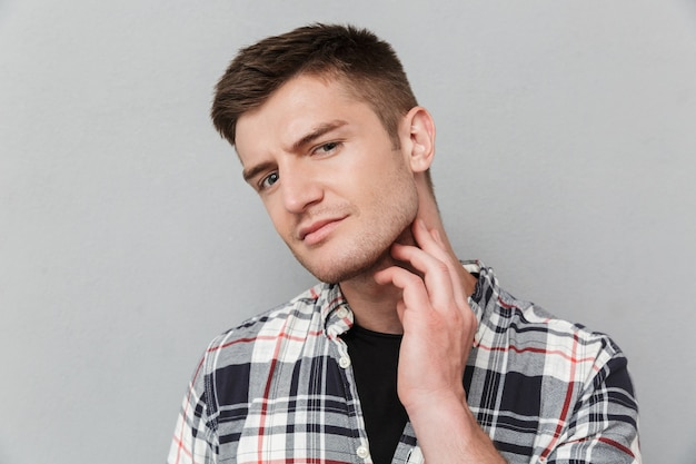 Portrait of a concerned young man in plaid shirt
