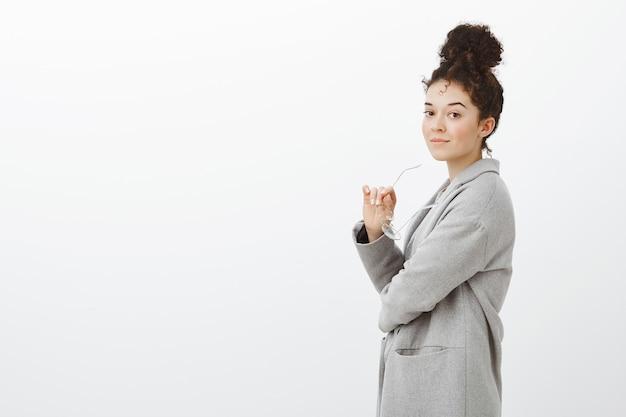 Ritratto di fiduciosa imprenditrice di successo in cappotto grigio alla moda, in piedi di profilo e sorridente sicura di sé, tenendo gli occhiali in mano, andando in metropolitana per lavorare