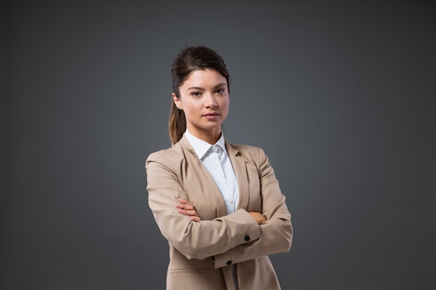 Portrait of a confident adult businesswoman standing in front of a gray wall with her arms crossed