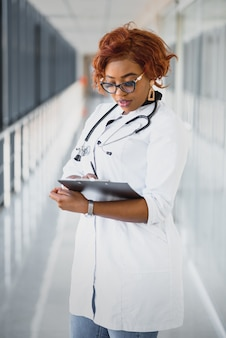 Portrait confident african american female doctor medical professional writing patient notes isolated on hospital clinic hallway windows background. positive face expression