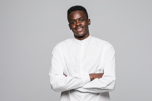 Portrait of confident  afro man dressed in white classic shirt with folded hands isolated on gray background