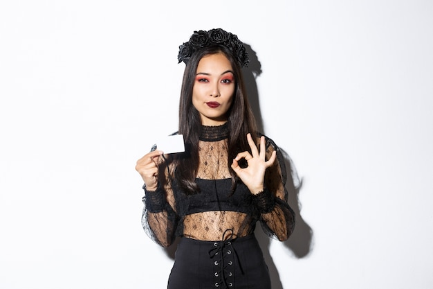 Portrait of confident asian woman assuring you in something, wearing halloween costume, showing okay gesture and credit card, white background.