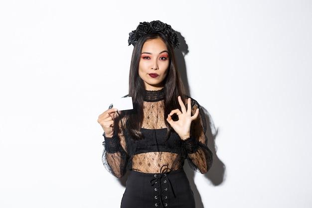 Ritratto di donna asiatica fiduciosa assicurandoti qualcosa, indossando il costume di halloween, mostrando gesto giusto e carta di credito, muro bianco