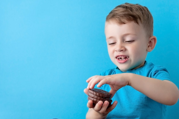 Portrait of confident attractive little boy holds american chocolate chip cookies on blue wall